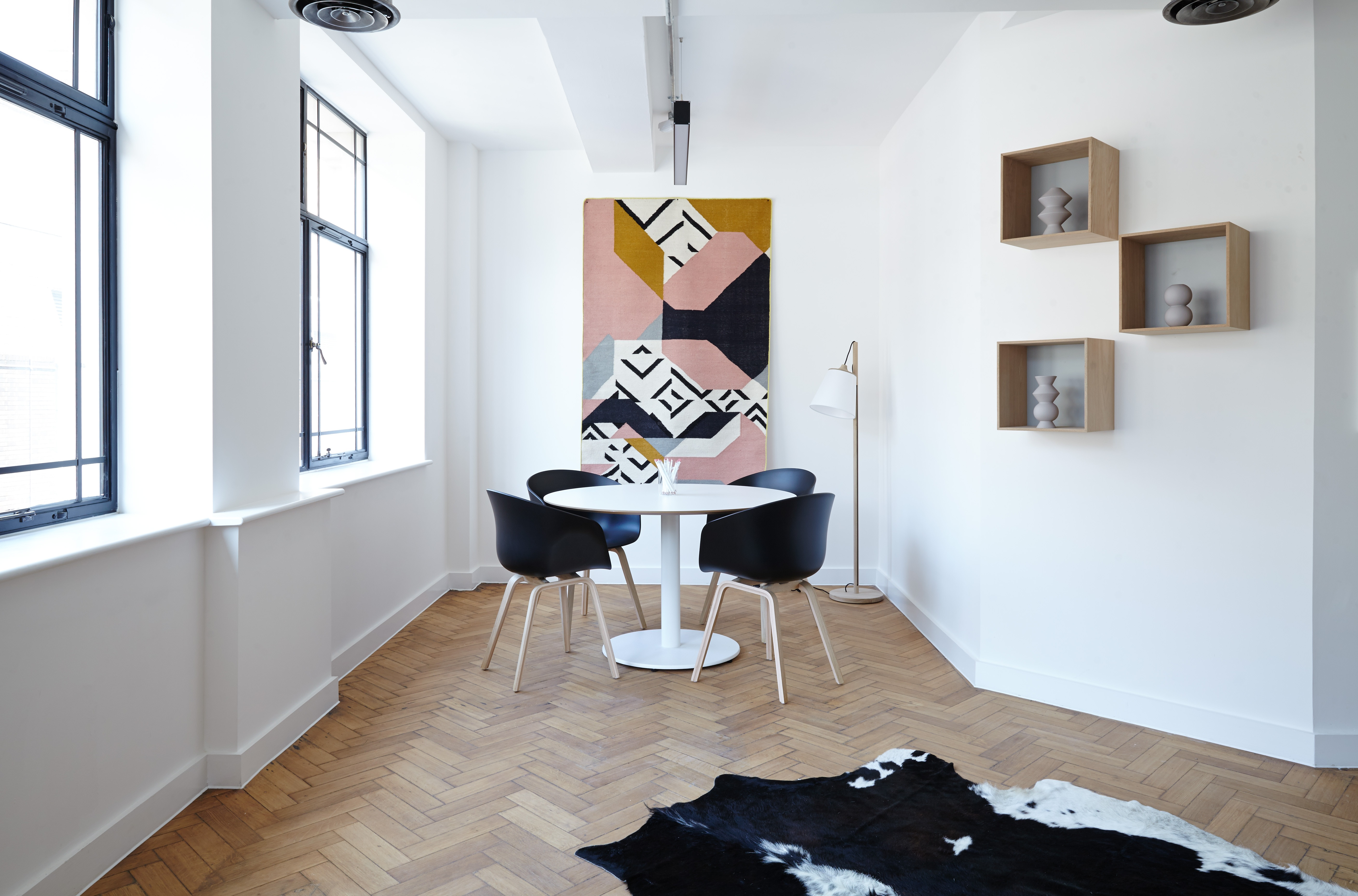 image of an apartment with plenty of natural light, wood flooring, a cowhide rug in the corner, and four black chairs around a circular white table. there are lightboxes and art on the walls.